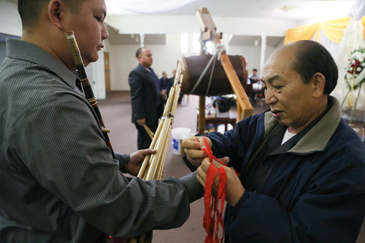 Cher Kal Xiong ties red ribbon to the wrist of Panh Vang, a txiv qeej or master qeej player, who is about to play the first song of the funeral called the qeej tu siav. The qeej is played to communicate directly to the spirit. The red ribbon protects the soul of the wearer from wandering away from his or her body. The first song is critically important during the Hmong funeral by leading the spirit to the spirit world where he or she will begin a journey to the birth village to reincarnate. Teng Her, another txiv qeej, prepares to beat the drum. The drum alerts anyone around the house that someone has passed away.