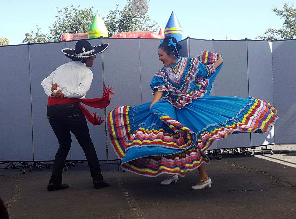 Ricardo Cortez and Alexis Rodriguez dancing in the traditional Jalisco region attire.